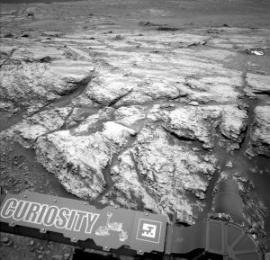 """Gray rocky area with nameplate saying 'Curiosity"""" in lower left corner."""