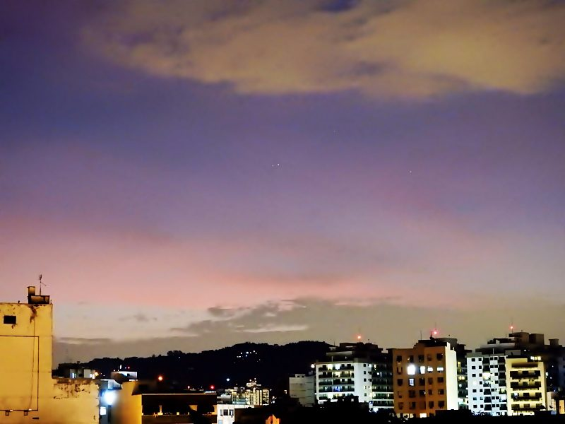 A colorful pink and blue twilight sky over cityscape, with 2 faint starry dots very close together.
