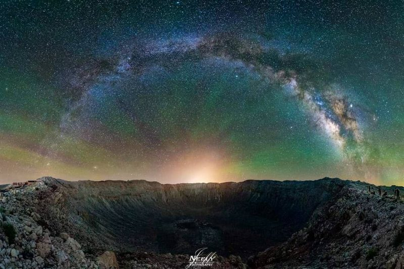 A deep crater, the Milky Way stretched above it, the light of Winslow shining along the crater rim, and streaks of green air glow.