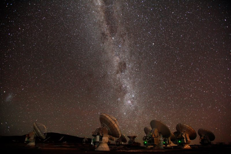 An array of dish-type radio telescopes, with the Milky Way stretched above them.