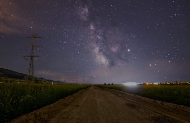 A country road, the Milky Way stretched above, stars and two bright dots.