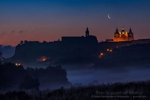 A darkened city at dawn, with the waning moon and Venus above.