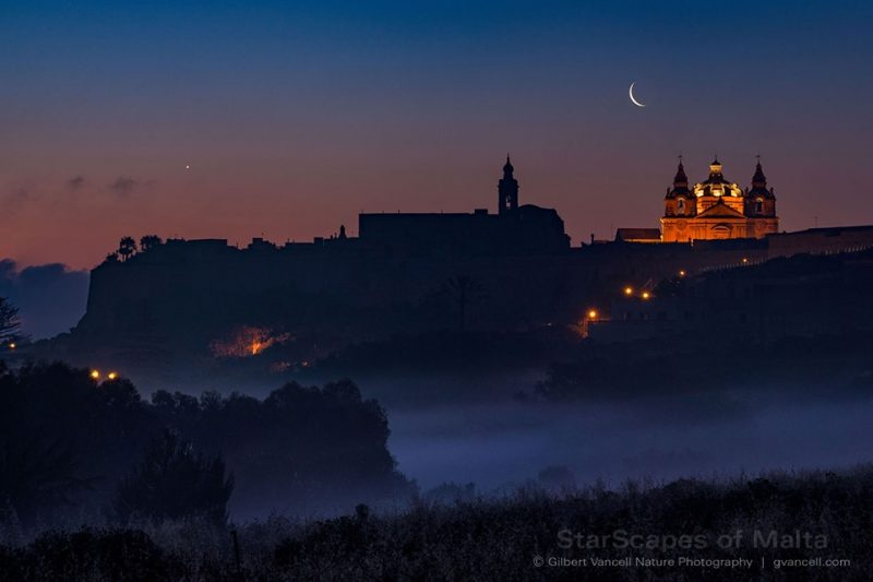 A darkened city at dawn, with the very thin crescent moon and tiny dot Venus above.