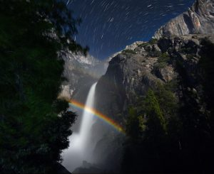 Rainbow over a rocky waterfall with star trails in night sky above.