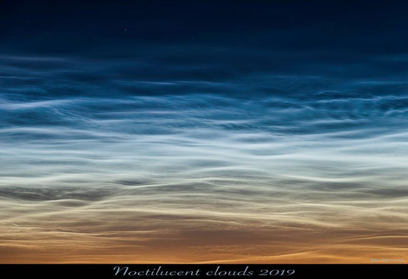 High, wavelike, glowing white clouds against deepening twilight sky.
