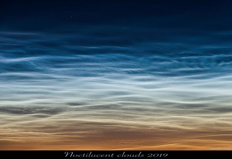 Wavy electric-blue clouds, shining at night far above the yellow horizon.
