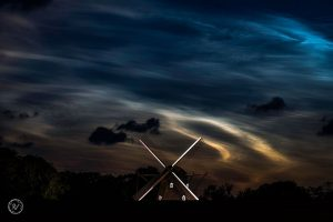 Electric blue and orange clouds light up the night sky behind a windmill.