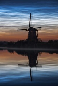 Shining blue clouds at night. Silhouette of windmill. Reflections in water.