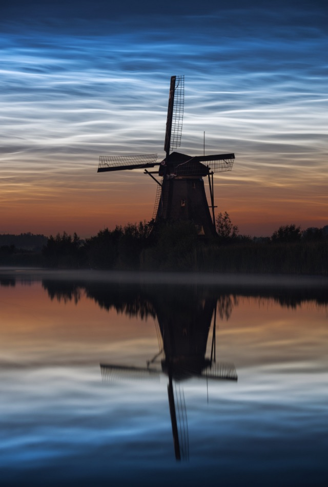 Shining blue clouds at night. Silhouette of Dutch windmill. Reflections in water.