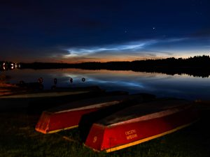 Colorful nighttime image of boats on a waterfront, with noctilucent clouds shining overhead.