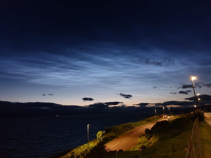 Blue shining clouds at night over perspective view of highway with street light to side.