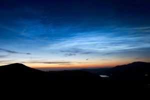 Electric blue clouds in night sky with thin orange line at the horizon.