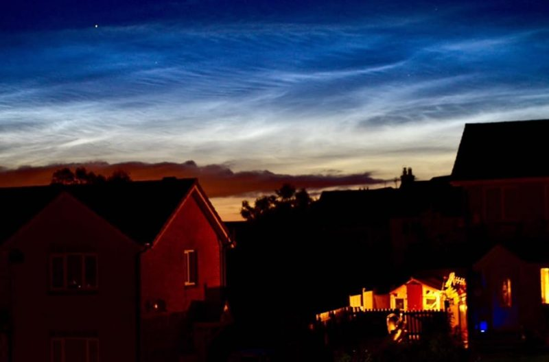 Illuminated evening clouds over houses with lights in the windows.