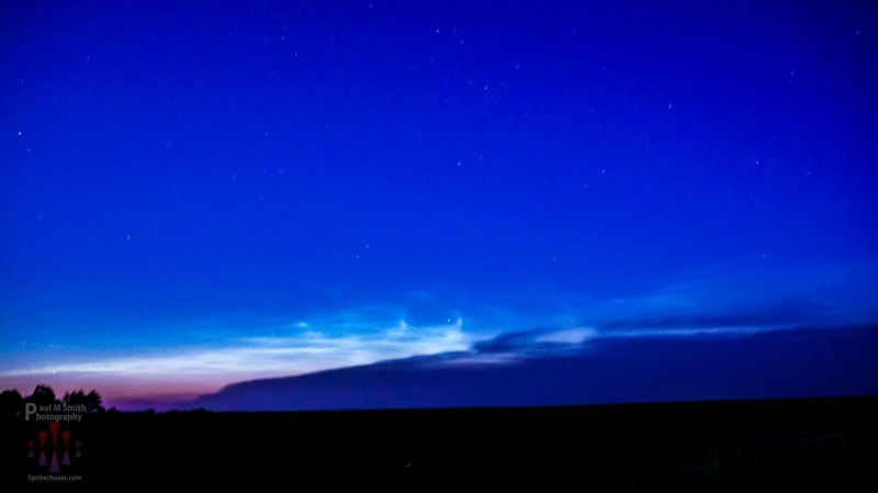 Shining clouds, low on the horizon, against deep cobalt sky.