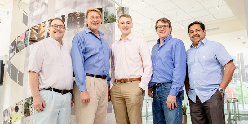 Five men in casual clothing standing beside each other smiling broadly.