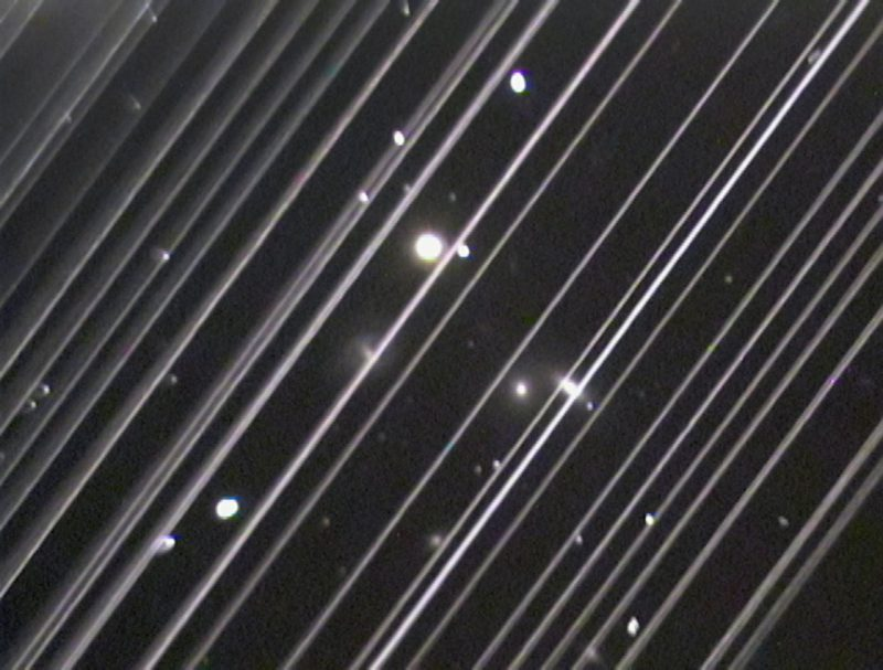 Many white diagonal lines across a black background. Irregular white dots behind them.