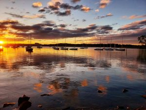 Sunrise over a lake, with many sailboats anchored, and clouds reflecting in the water.