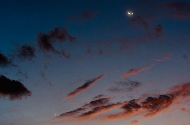 A twilight sky, with reddened, sunlit clouds, and a thin crescent moon and Venus.