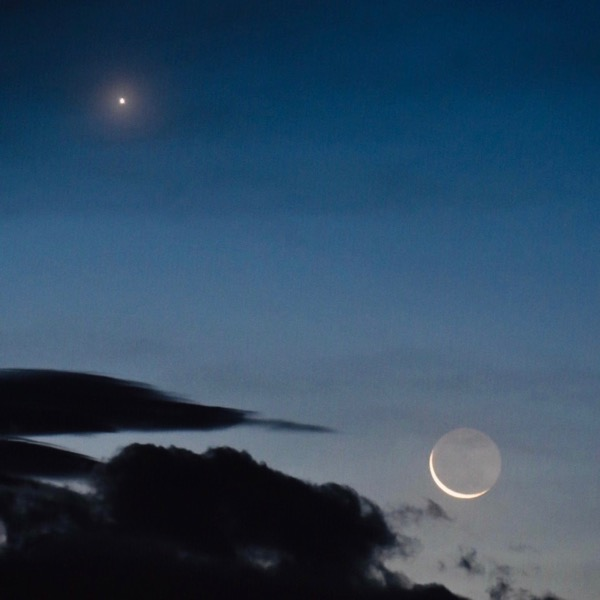 Bright dot and extremely thin crescent moon with the rest of the moon softly shining in a slate-blue sky.
