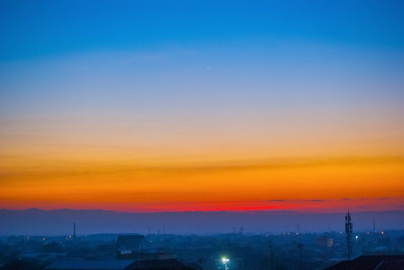 Sky fading from brilliant orange to blue over a misty town, with Venus high in the sky.