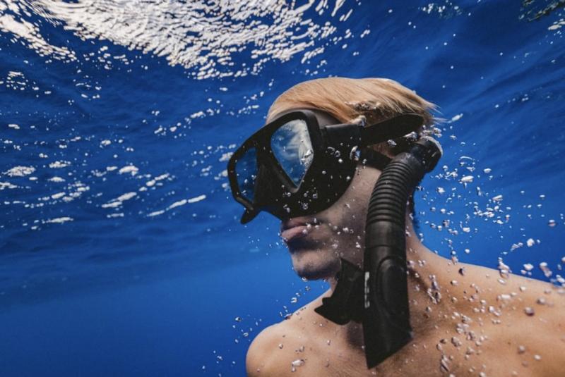 Blonde man underwater wearing big goggles and scuba equipment.