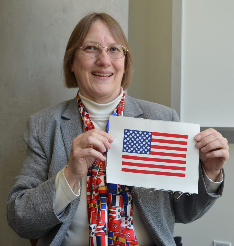 A woman wearing a scarf printed with flags of all nations, holding a small US flag.