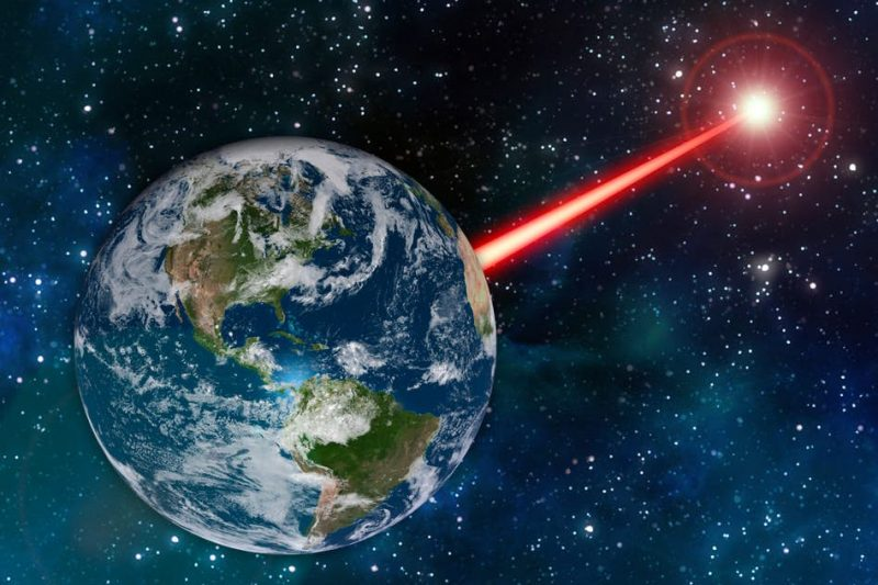 Laser light beam from glowing object in space, pointed toward globe of Earth against starry sky.