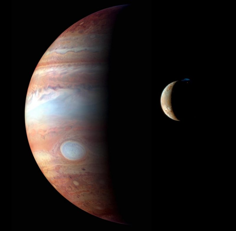 Large crescent banded planet with small varicolored moon in front of it.