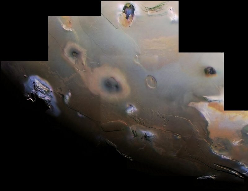 Io's mottled terrain. Gray background with large irregular black and blue spots.