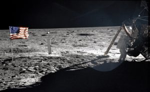 US flag, astronaut, Apollo 11 spacecraft and its shadow on the moon.