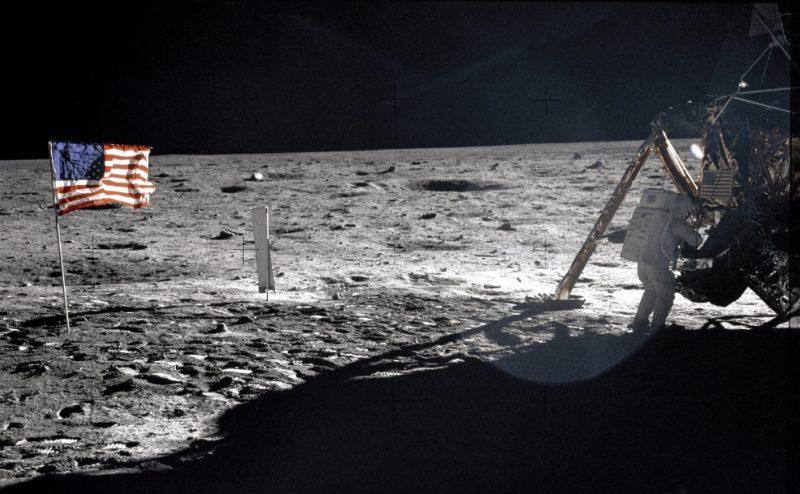 US flag, astronaut near bent leg of Apollo 11 lunar lander. Lander's shadow on the gray lunar surface. Black sky.
