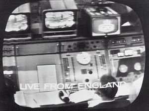 1962 style mission control panels with tv monitors above and man watching