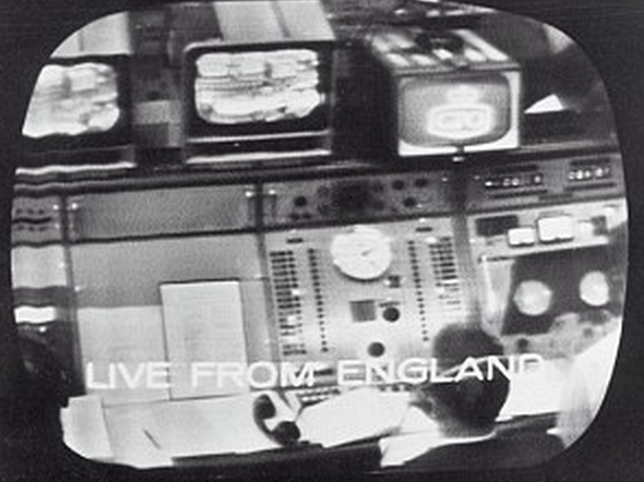 1962 style control panel with lots of buttons & dials & a man watching low resolution tv monitors.