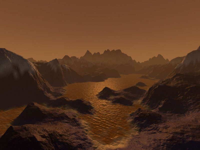 Steep mountains surround reddish lake under dim, pale tan sky.