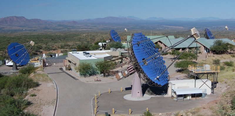 Four bright blue dish-style telescopes and buildings.