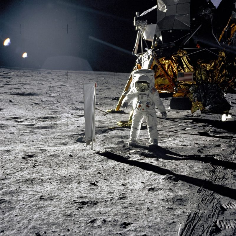 Astronaut in space suit in front of the boxy, partly gold lunar lander on a gray rocky landscape.