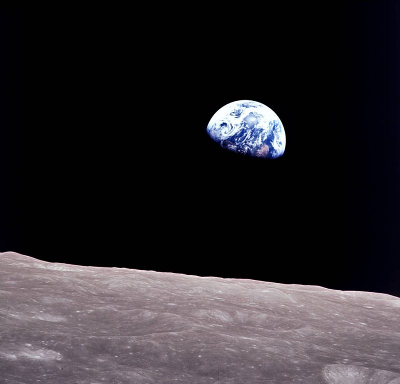 Blue and white Earth hanging in space against black sky with lunar landscape seen from orbit below.
