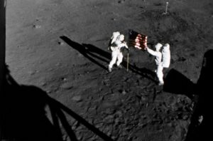 2 astronauts in spacesuits holding a US flag on the moon.