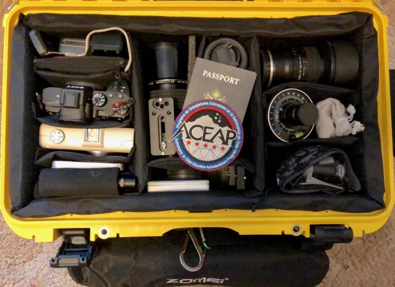 A suitcase full of camera equipment with a passport.