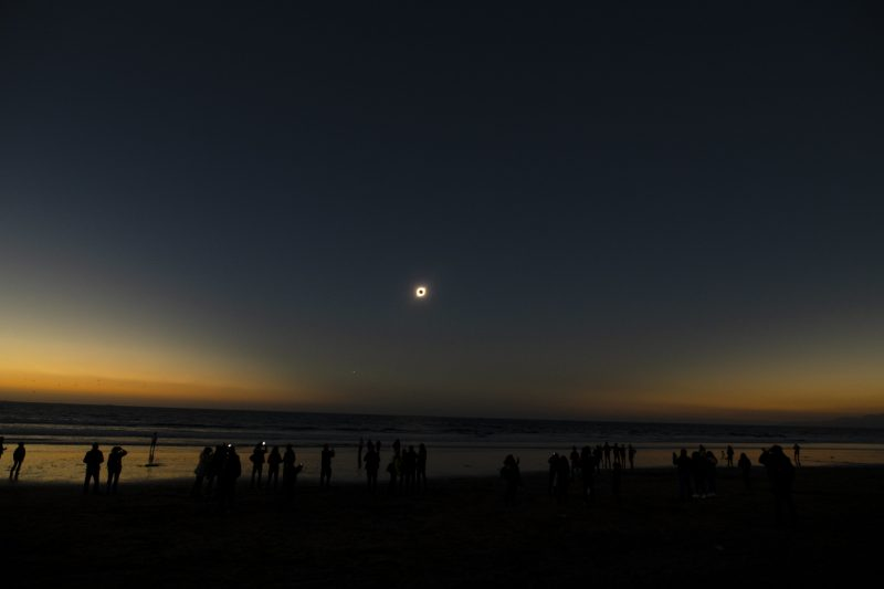Sun midway up in the sky, the black moon silhouette in front of it, people stand on a beach under a darkened sky.