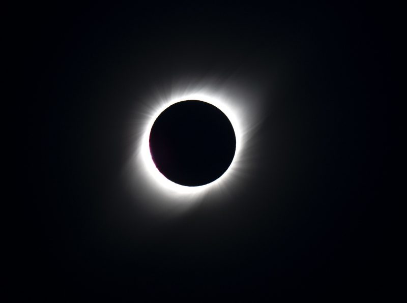 Dark moon silhouette with the fiery corona surrounding it.