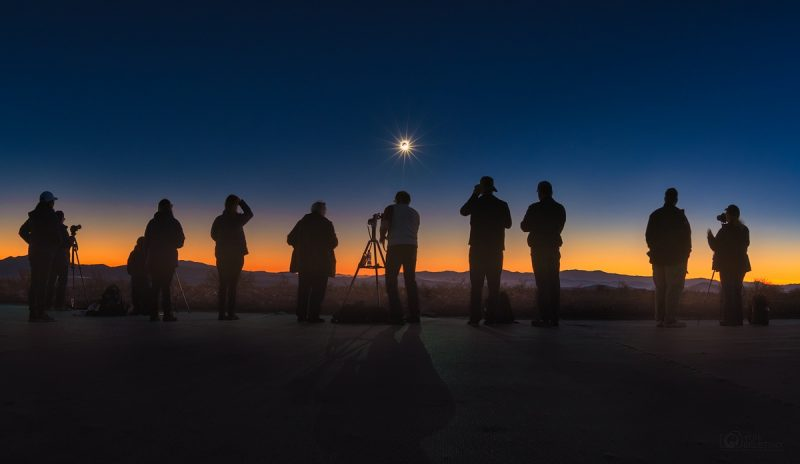Nine silhouetted standing people with the tiny-appearing eclipsed sun in the dark sky.