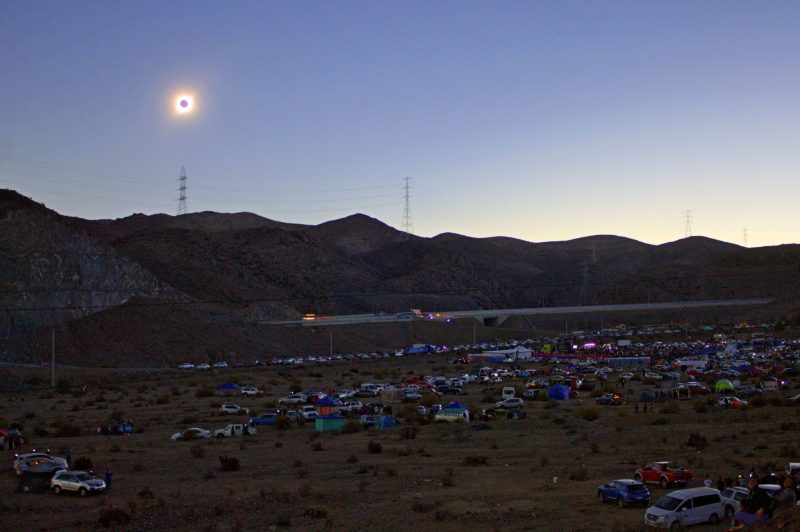 Totally eclipsed sun in darkened sky over a desert campground. Background: hills with distant pylons.