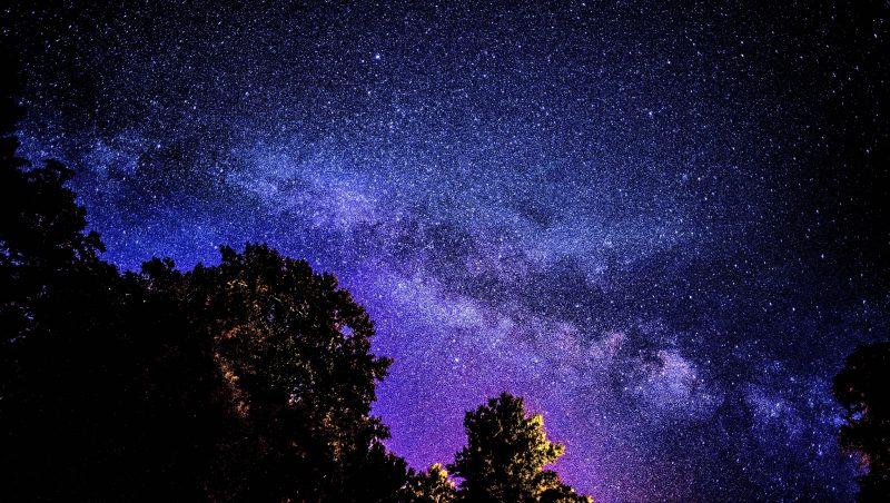 Starry Milky Way band, divided by irregular dark dust streak along its length.