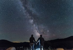 A couple holding hands under the Milky Way, with bright Jupiter shining to one side.