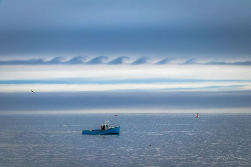 Clouds that look ocean waves over gray-blue water with a small tugboat on it.