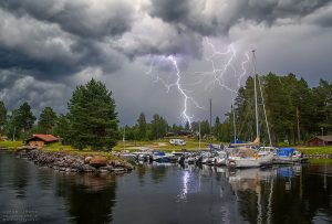 Lightning in a gray cloudy sky over a small harbor with sailboats.