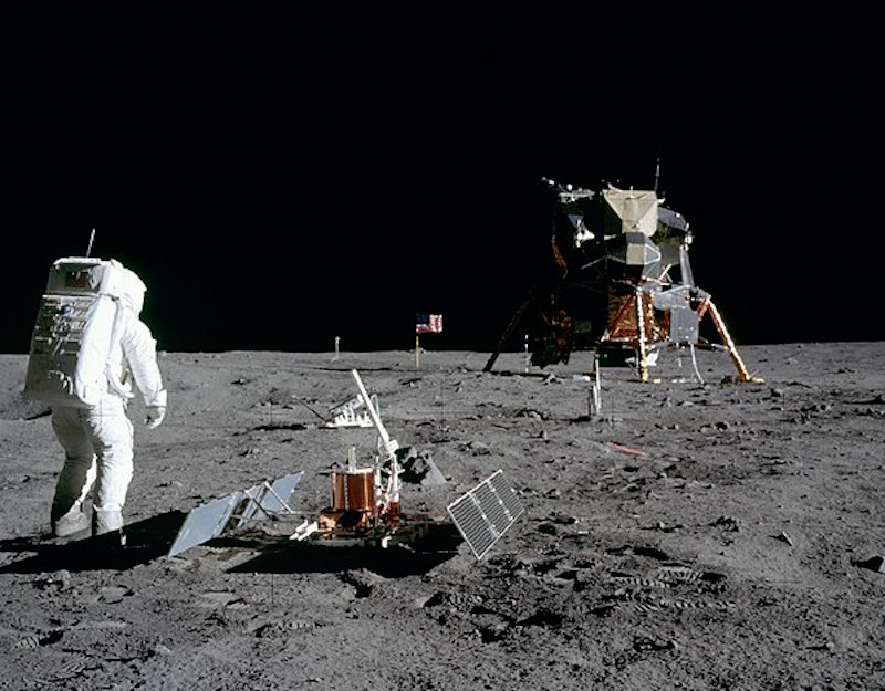 Moon-suited astronaut, gray landscape, black sky, lunar lander, equipment on ground, flag in distance.