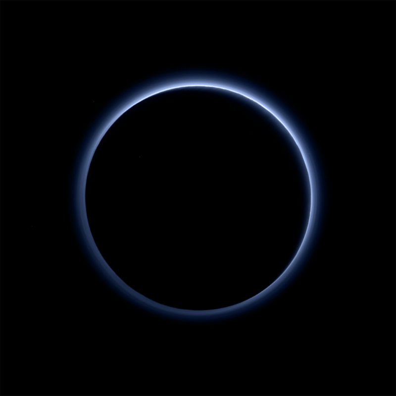 Dark circular silhouette of backlit Pluto, surrounded by ring of blue haze.