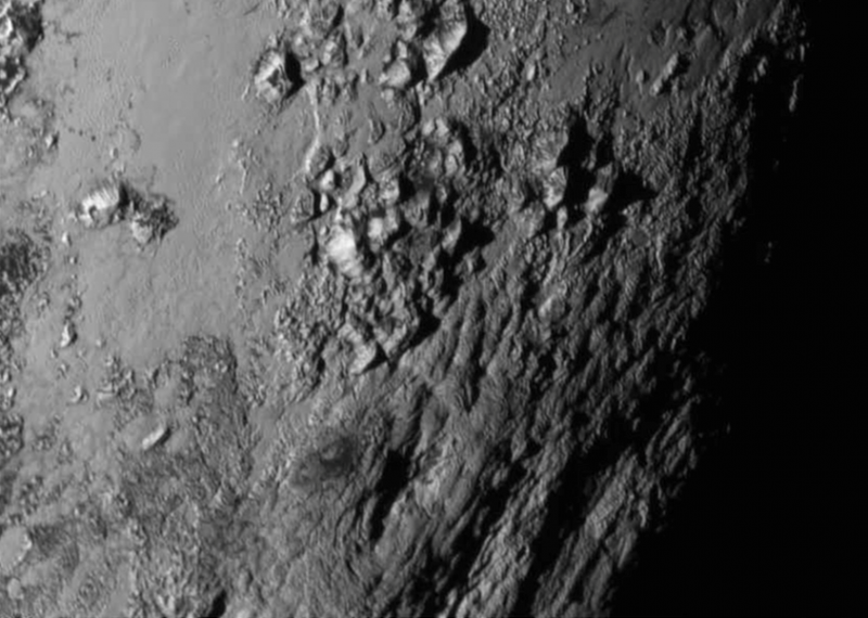 Raised, elongated mountains on right side of orbital image of Pluto.